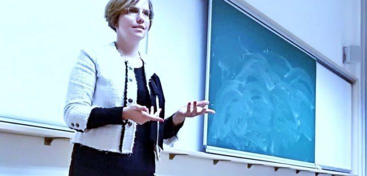 Sylwia Chrabałowska na tle ściany w sali wykładowej