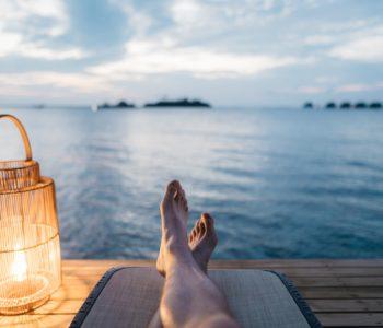 widok na nogi osoby leżącej i patrzącej w dal na wodę obok lampa